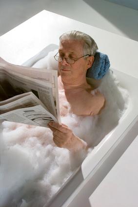 Senior nimmt mittels Badewanneneintritt ein Schaumbad.